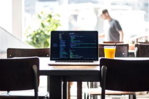 laptop on wooden table displaying code for web development