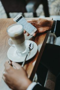 Person checking their email while drinking coffee