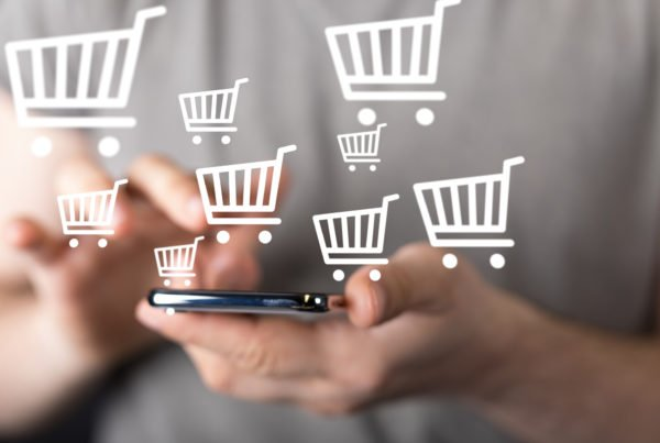 closeup of person using their phone to complete a purchase with shopping cart icons sales and marketing strategy